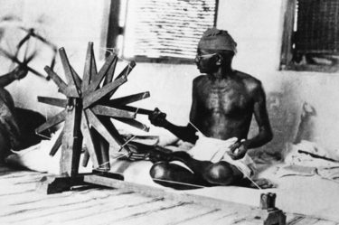 Mahatma Gandhi sits cross-legged and spins cotton in Ahmadabad, India, in this photo taken circa 1931.
